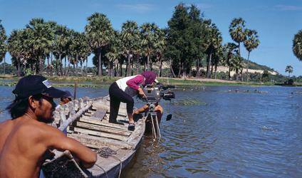 Photographie d'une journaliste cambodgienne filmant à partir d'une embar