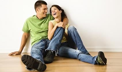 Jeune couple assis sur un plancher de bois.