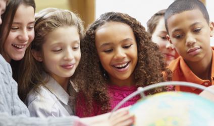 Photographie d'enfants d'âge scolaire devant un globe-terrestre.