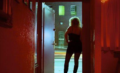 Photo d'une femme de dos adossée à une porte.