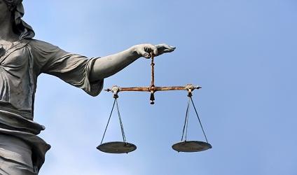 Image d'une statue personifiant la justice avec une balance.