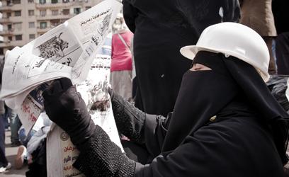 Photographie d'une femme en burqa, coiffée d'un casque.