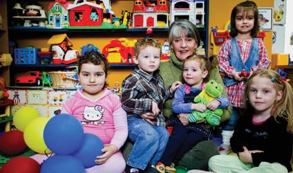 Photographie d'Odette Chartrand avec des enfants de sa garderie.