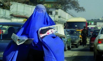 Photographie d'une femme afghane transportant des journaux