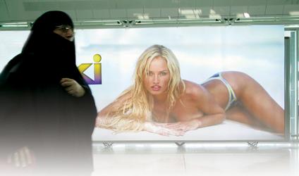 Photographie d'une femme voilée derrière une affiche sexy