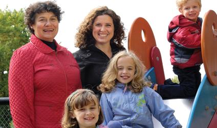 Photographie de deux mamans et de 3 enfants sur une glissade de parc