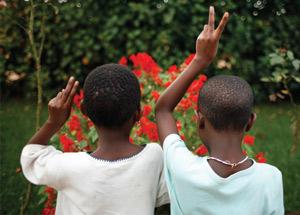 Photographie de 2 enfants montrant le signe paix avec leurs doights