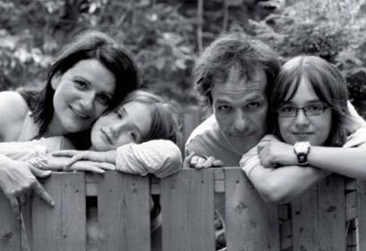 Photographie d'une famille accotée sur une clôture en bois