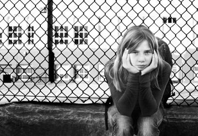 Jeune fille assise devant une clôture.