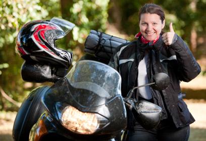 Une femme enfourchant une moto.