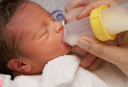 Nourisson buvant à une bouteille de lait.