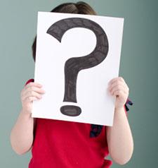 Jeune enfant tenant une pancarte devant elle avec un point d'interrogation