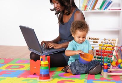 Photographie d'une femme qui travaille à côté de son enfant qui joue