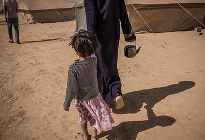 Une femme réfugiée tenant une enfant pas la main.