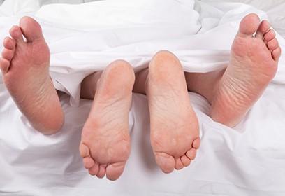 Photographie d'un couple au lit, sous les couvertures
