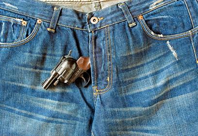 Photographie de jeans avec un fusil qui sort de l'entrejambe