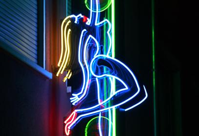 Photographie de l'insigne lumineuse d'un bar de danseuses nues