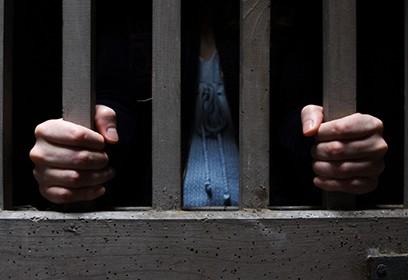 Photographie d'une personne dans une cellule de prison.