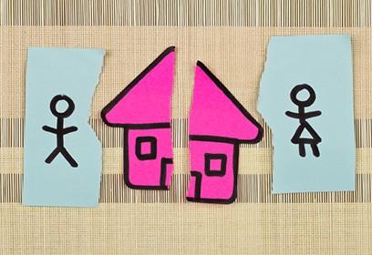 Photographie d'une maison de papier déchirée en deux