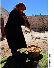 Aïcha Asbban versant des amandons dans un panier d'osier.