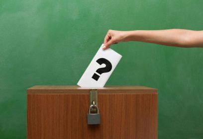 Photographie d'une personne remettant son buletin de vote dans l'urne