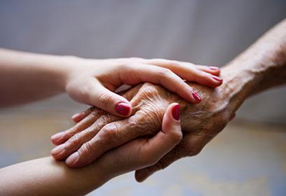 Photographie de deux jeunes mains qui en tiennent une vieille.