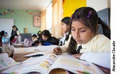 Photographie de Gissela en classe lisant un livre scolaire.