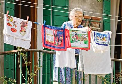 Photographie d'une femme âgée faisant sécher du linge