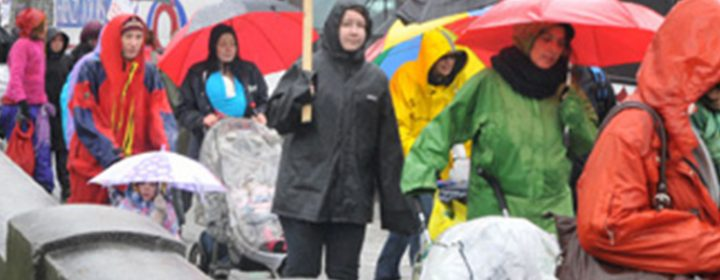 Photographie de marcheuses sous la pluie lors d'une manifestation.