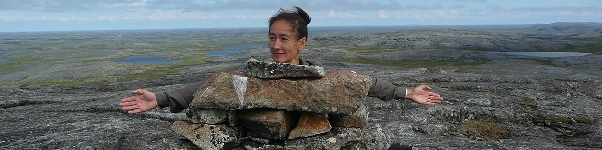 Photographie de Lisa Koperqualuk derrière un Inukshuk.