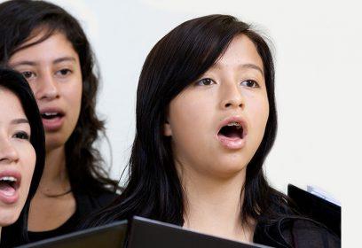 Photographie de trio de jeunes femmes qui chantent.