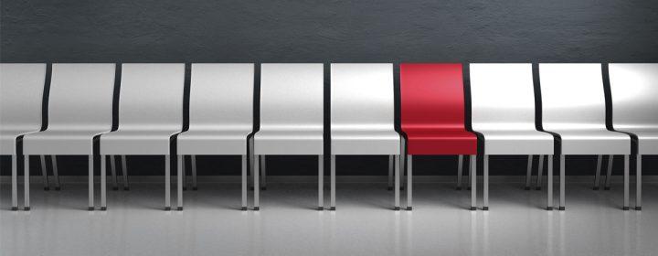 Photographie d'une chaise rouge parmi un grand nombre de chaises grises