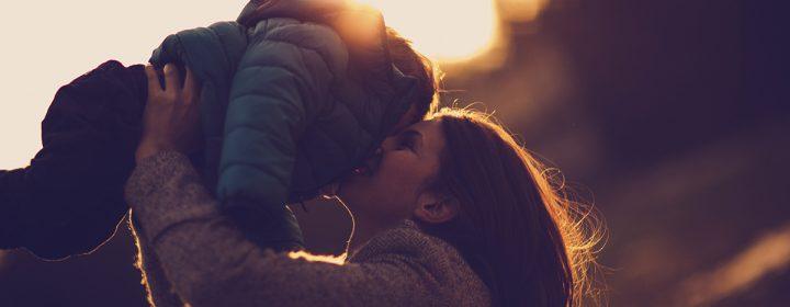 Jeune femme soulevant son enfant en l'embrassant.