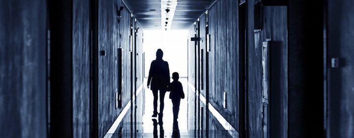 Une mère tenant son enfant par la main dans un corridor.