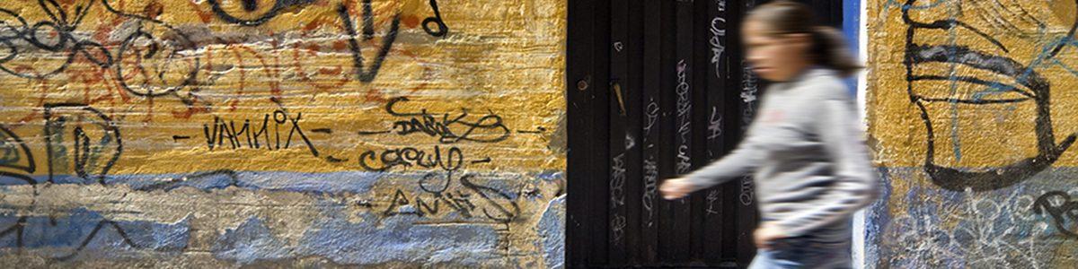 Femme marchant devant un mur avec graffiti.