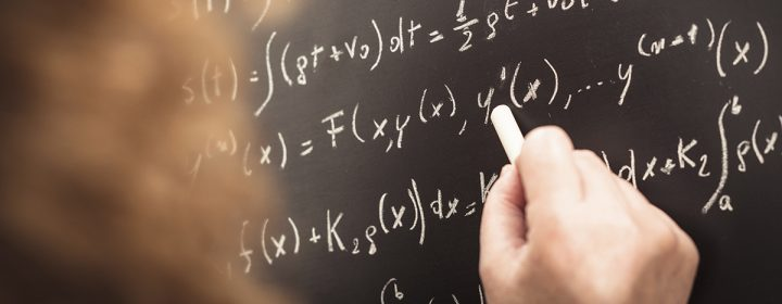 Femme inscrivant formules mathématiques sur un tableau.