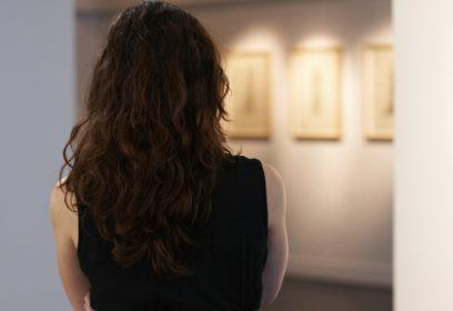 Photographie une jeune femme vue de dos, regardant dans le foyer d'une galerie.
