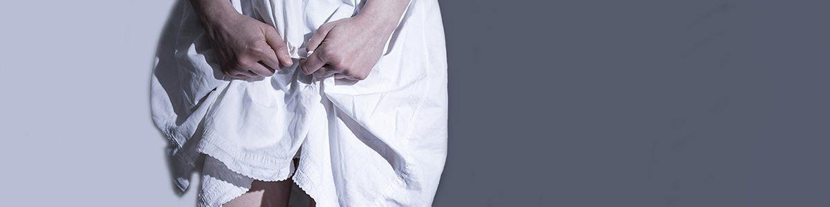 Femme tenant le bas de sa robe relevée avec ses deux mains.