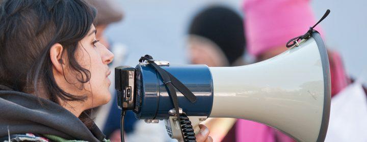 Jeune femme utilisant un haut-parleur lors d'une manifestation.