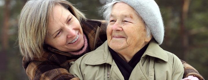 Une proche aidante tient une vieille femme dans ses bras.