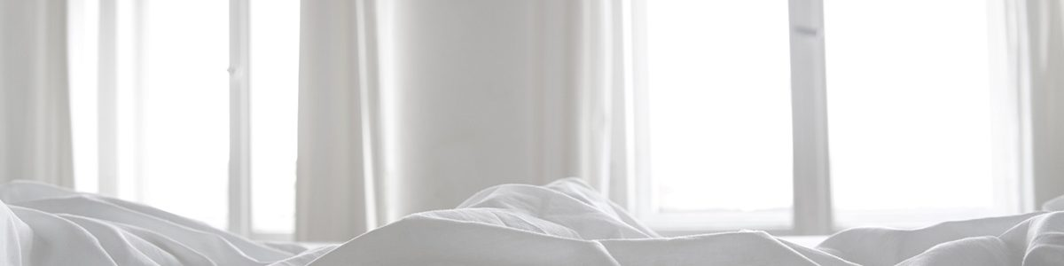 Dessus de draps blancs avec fenêtres ouvertes.