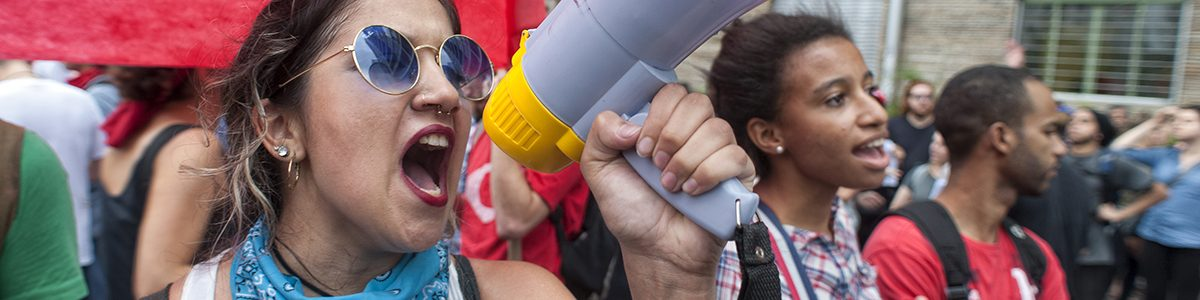 Femme avec un mégaphone à une manifestation.