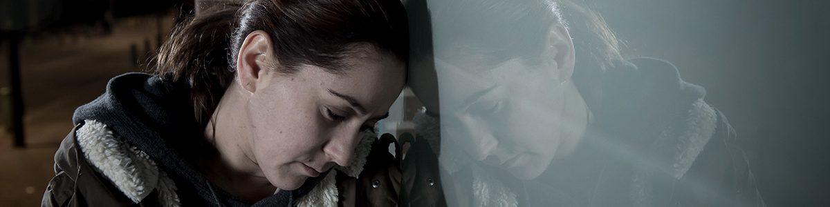 Jeune femme appuyée sur un mur.