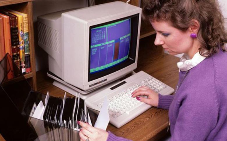 Jeune femme travaillant sur ordinateur des années 1970.