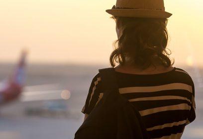 Femme de dos regardant un avion.