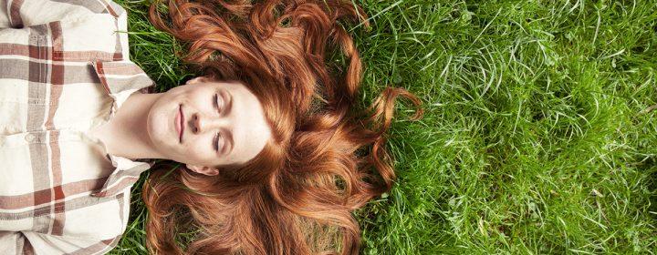 Jeune adolescente couchée dans le gazon.