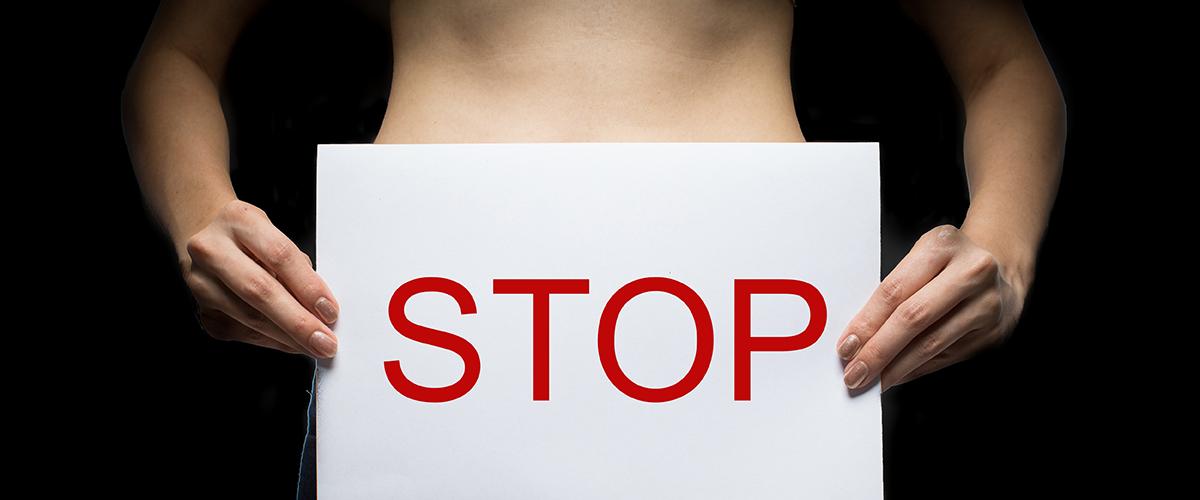 Femme tenant une affiche stop.