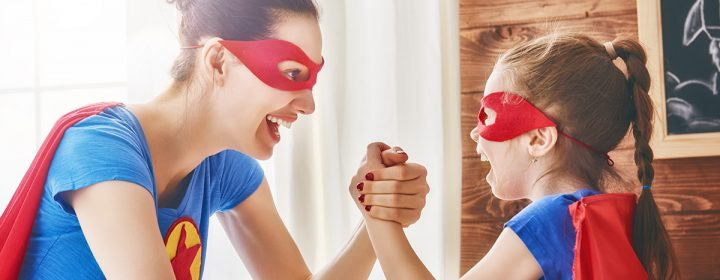 Mère et fille déguisée en super héros rigolant ensemble.