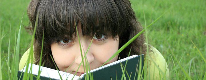 Jeune fille couchée dans le gazon, avec un livre ouvert.
