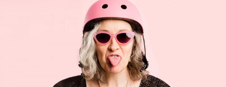 Femme avec un casque et des lunettes rose et faisant une grimace.